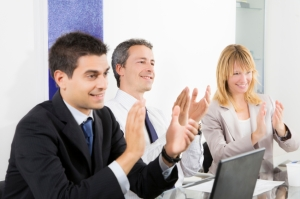 Businesspeople clapping in business meeting.