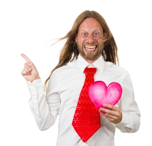 Funny hippie man holding a love heart and pointing